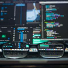 Pair of glasses placed in front of a desktop screen with data